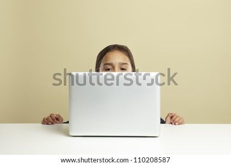 Young girl using laptop on white desk