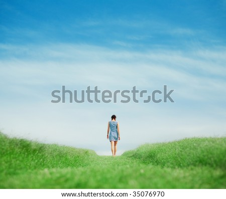 Young girl walking on grass field