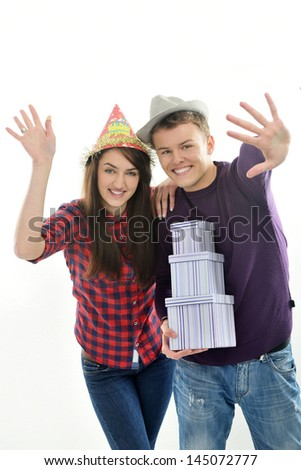 Young girl waving and leaning onto a young man with hat waving and holding three boxes isolated on white