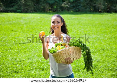 Young girl with a basket of vegetables and fruits outdoors