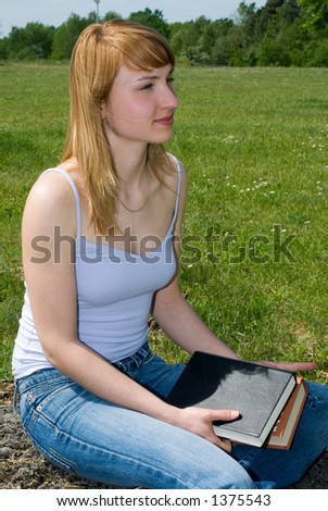 young girl with a book outside