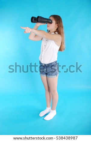 Young girl with binoculars isolated on blue background