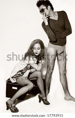 young girl with cigarette in kortkom dress sitting at the feet of  guy in swimming trunks and sunglasses