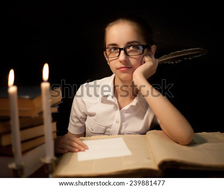 Young girl writing with feather. Candle and book near