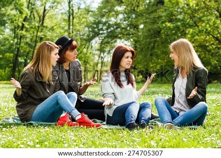 Young girls are sitting in the park and arguing because of something.Conflicts between friends