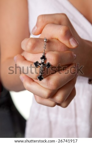 Young girls hands folded in prayer with a cross young girls hands folded in prayer with a cross