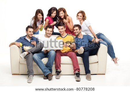 young group of friends sitting on couch smiling at laptop