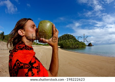 Young guy drinking fresh coconut on a sandy beach of a tropical island
