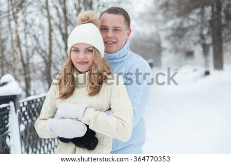 Young guy hug his girlfriend in winter park