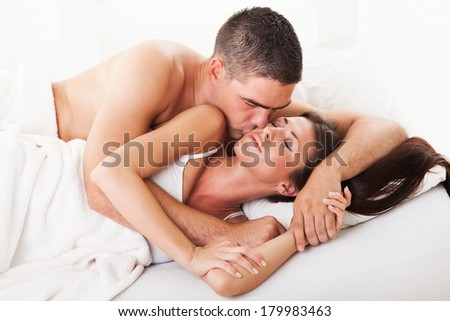 Young guy kissing his girl on the cheek for good morning in the bed.