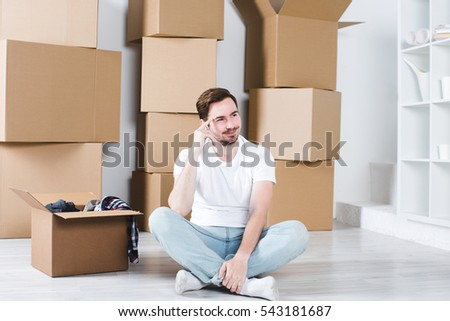 Young guy sitting on the floor of new house surrounded with boxes. Moving in new home.