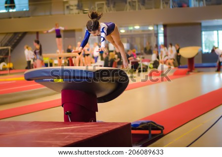Young gymnast girl performing jump on a vault while practicing for the competition