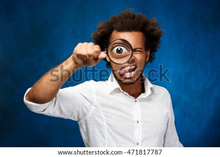 Young handsome african man posing with magnifier over blue background.