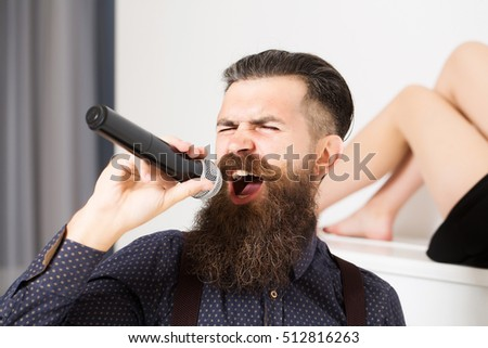 young handsome bearded man singing in microphone with pretty sexy cute woman or girl in black dress laying on white piano in studio