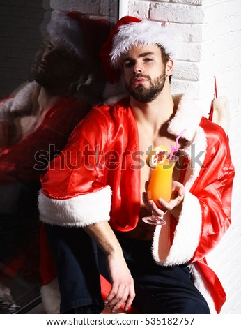 young handsome bearded sexy christmas man in red santa claus hat and coat with muscular bare torso sitting on windowsill and holding glass of alcoholic cocktail on black and brick wall background