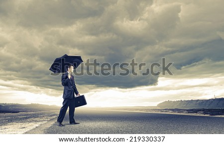 Young handsome businessman standing on asphalt road