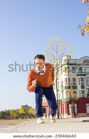 young handsome casual man ready to run and for quick start on the sidewalk in  old city and looking at camera , retro vintage fashion composition