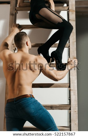young handsome macho man in jeans with sexy muscular athletic body with bare torso has strong back with female legs in black shoes and stockings in studio at wooden ladder