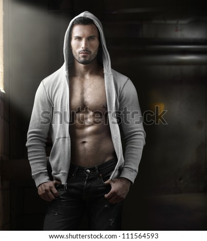 Young handsome macho man with open jacket revealing muscular chest and abs in industrial garage with window light