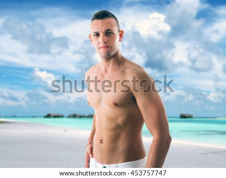 Young handsome man enjoying his vacation on the beach