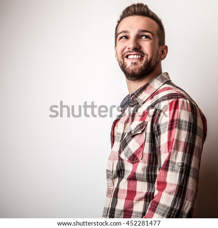 Young handsome man in colorful shirt pose in studio.