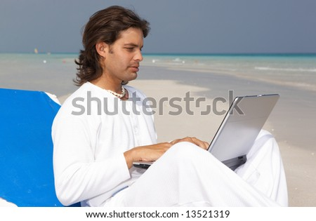 Young handsome Man on the beach using laptop