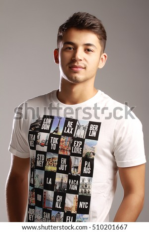 young handsome man posing againts gray background