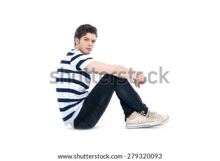 young handsome man sitting floor . Studio fashion portrait
