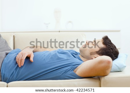 Young Handsome Man Sleeping On Couch At Home Side View