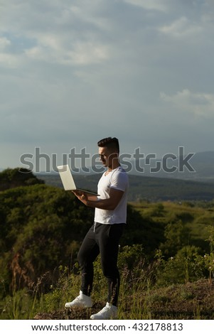 Young handsome man with muscular sexy body standing with laptop outdoor sunny day on blue sky background