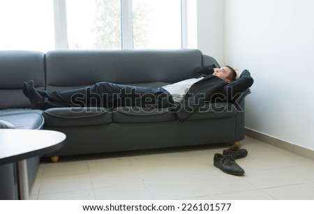 Young Handsome Office Man Lying on the Gray Couch at Lounge Area During Work Break Hours.