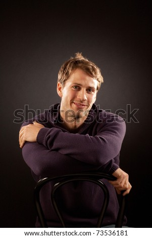 Young handsome relaxed blonde man sitting on a chair smiling against dark background