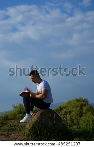 Young handsome serious man with muscular sexy body and bare chest sitting with laptop outdoor sunny day on blue sky backdrop