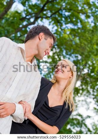 Young happy attractive embracing couple, outdoors. Love, flirt, romantic, relations theme concept.