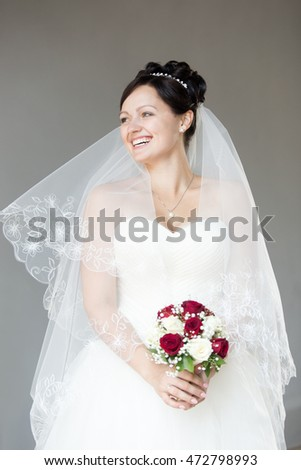 Young happy beautiful bride holding bridal bouquet with white and red roses. Attractive bride with fashion wedding hairstyle wearing diadem and veil over shoulders looking sideways and laughing