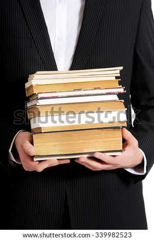 Young happy businessman holding stack of books.