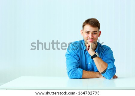 Young happy businessman in blue shirt sitting at the table in office