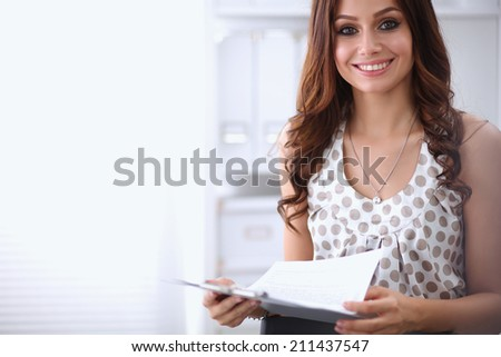 Young happy businesswoman in office holding a folder