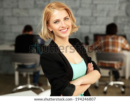 Young happy businesswoman standing on office