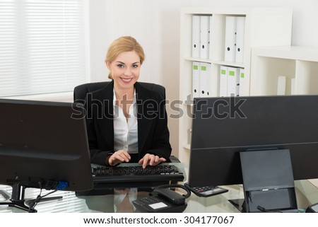 Young Happy Businesswoman Working On Computer At Desk