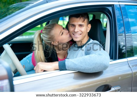 young happy couple in car smiling and kissing