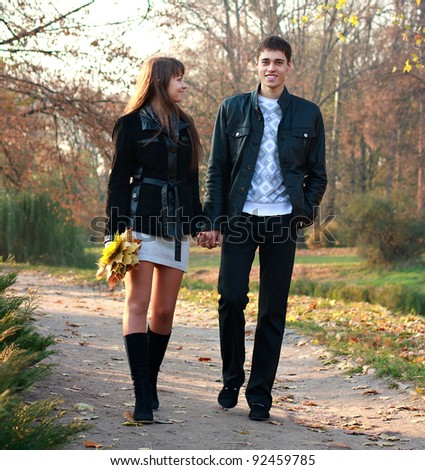 Young happy couple in love walking in park holding hands against the background of autumn nature