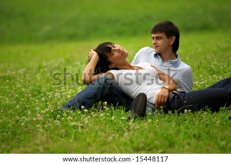 Young happy couple in park on a grass