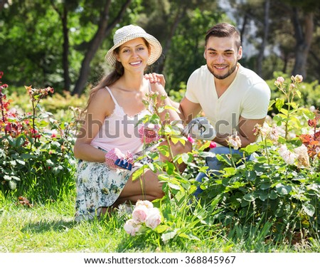 Young happy couple is engaged in gardening together