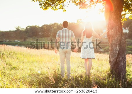 Young happy couple standing on the field, hand in hand, on the sunset