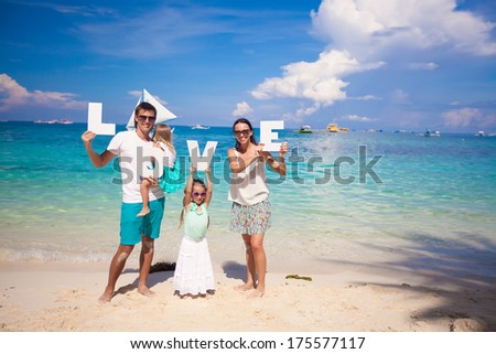 Young happy family of four on tropical vacation with word LOVE