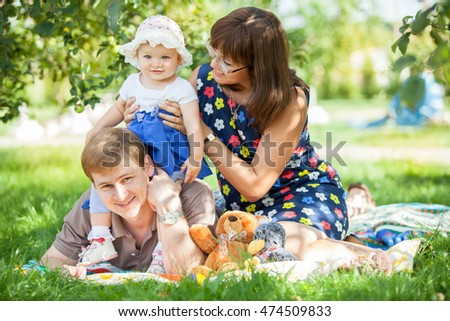 Young happy family sitting in the Park on the lawn
