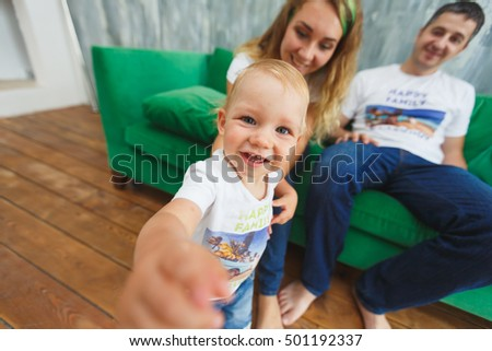 young happy family sitting on a green couch in the room. Baby boy sitting on his father's lap