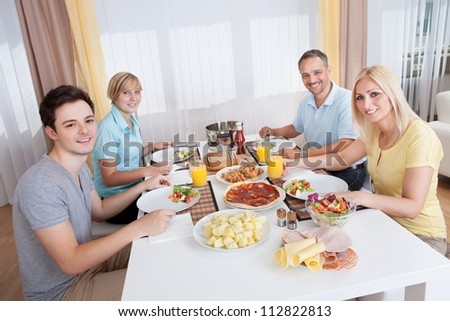 Young happy family with teenage children sitting down to eat a cold lunch of meat and salads