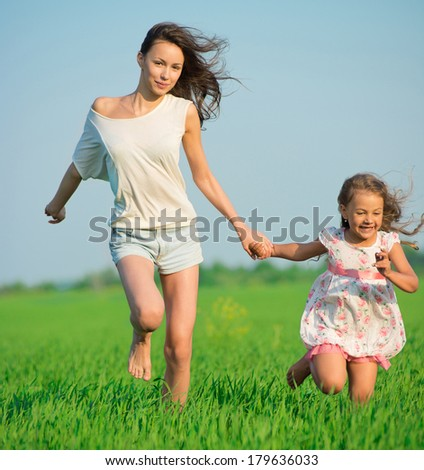 Young happy girls running down green wheat field with her friend together